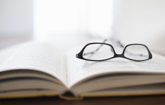 Eyeglasses sitting on open textbook